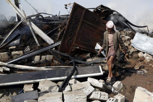 A man walks on the wreckage of a store of vehicle oil and tyres targeted by airstrikes carried out by the Saudi-led coalition on July 02, 2020 in Sana'a, Yemen [Mohammed Hamoud/Getty Images]