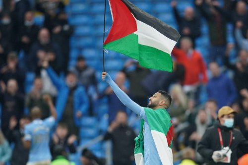 Riyad Mahrez of Manchester City wears the flag of Algeria, as he carries the flag of Palestine after Manchester City are presented with the Premier League Trophy following their victory in the Premier League match between Manchester City and Everton at Etihad Stadium on 23 May 2021 in Manchester, England. [Dave Thompson - Pool/Getty Images]