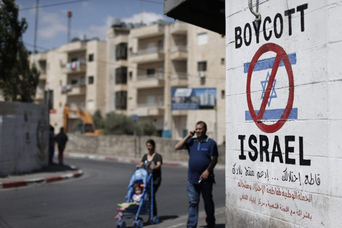 Palestinians walk past a sign painted on a wall in the West Bank biblical town of Bethlehem on June 5, 2015 [THOMAS COEX/AFP via Getty Images]