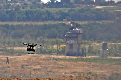 This picture taken from the southern Israeli kibbutz of Nahal Oz across the border with the Gaza Strip shows an Israeli army drone flying over Palestinian protesters on June 8, 2018 [JACK GUEZ/AFP via Getty Images]