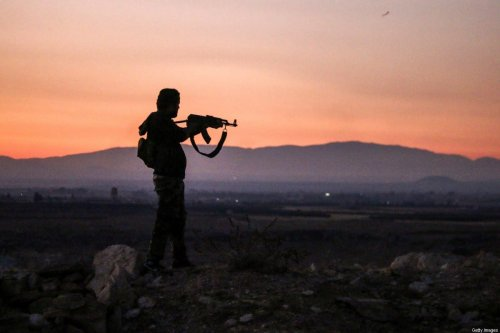 TOPSHOT - A Syrian rebel fighter aims his Kalashnikov assault rifle as he stands near the frontline against government forces west of the embattled southern city of Daraa on July 3, 2018. (Photo by Mohamad ABAZEED / AFP) (Photo credit should read MOHAMAD ABAZEED/AFP via Getty Images)