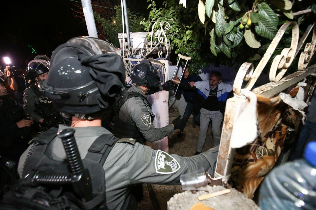 Israeli forces force a door of a Palestinian family to raid the house as Palestinians gather to stage a demonstration at Sheikh Jarrah neighbourhood after Israeli government's plan to force some Palestinian families out of their homes in East Jerusalem on 6 May 2021 [Mostafa Alkharouf/Anadolu Agency]