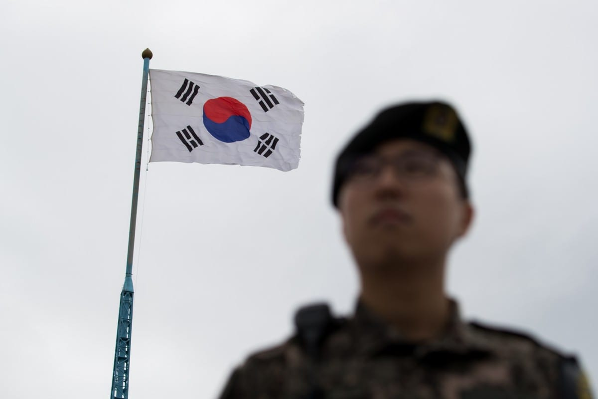 A South Korean soldier stands guard in front of a South Korean flag in South Korea, on 24 April 2018 [SeongJoon Cho/Bloomberg/Getty Images]