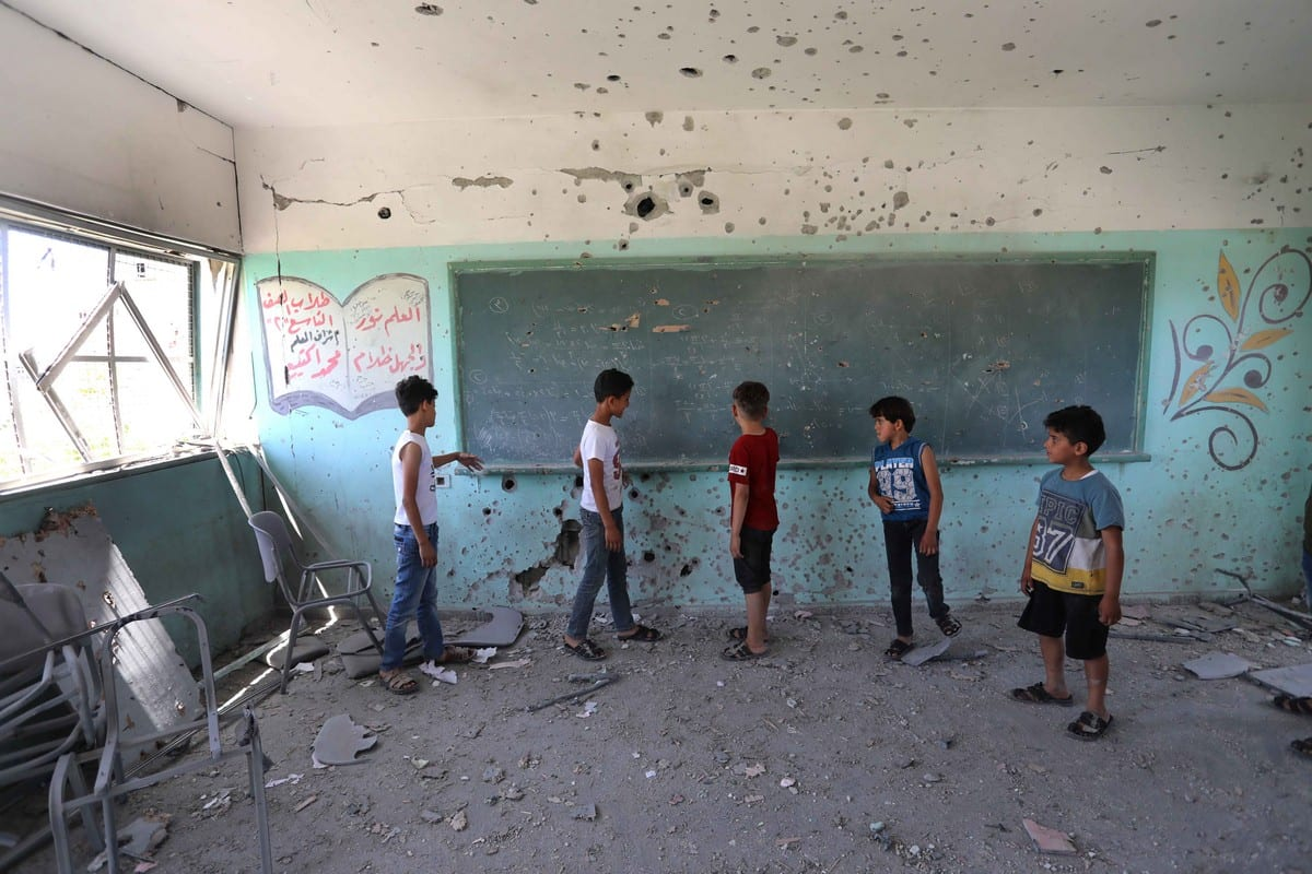 Children are seen inside a damaged school in the aftermath of Israeli attacks that began on May 10 and continued for 11 days in Gaza City, Gaza on 26 May 2021 [Ashraf Amra/Anadolu Agency]