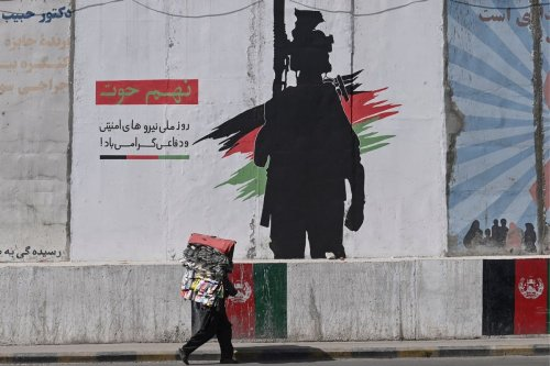 A street vendor walks past a mural depicting an Afghan National Army soldier in Kabul on 10 June 2021 [ADEK BERRY/AFP/Getty Images]