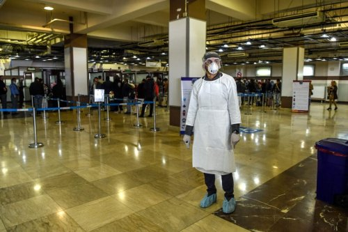 A health services staff member wearing protective gear looks on as he waits to check passengers at the Hamid Karzai International Airport in Kabul on February 2, 2020 [WAKIL KOHSAR/AFP via Getty Images]