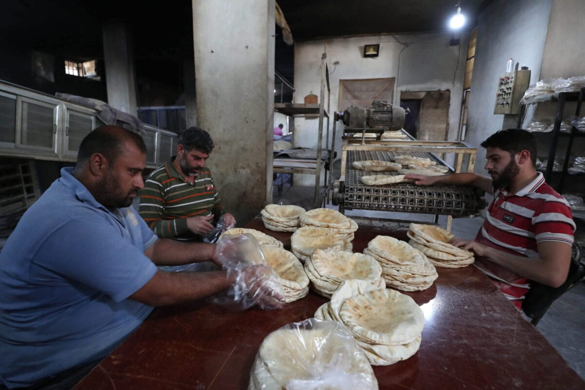 Syrians pack bread at a bakery in the town of Binnish in the country's northwestern Idlib province on June 9, 2020 [OMAR HAJ KADOUR/AFP via Getty Images]