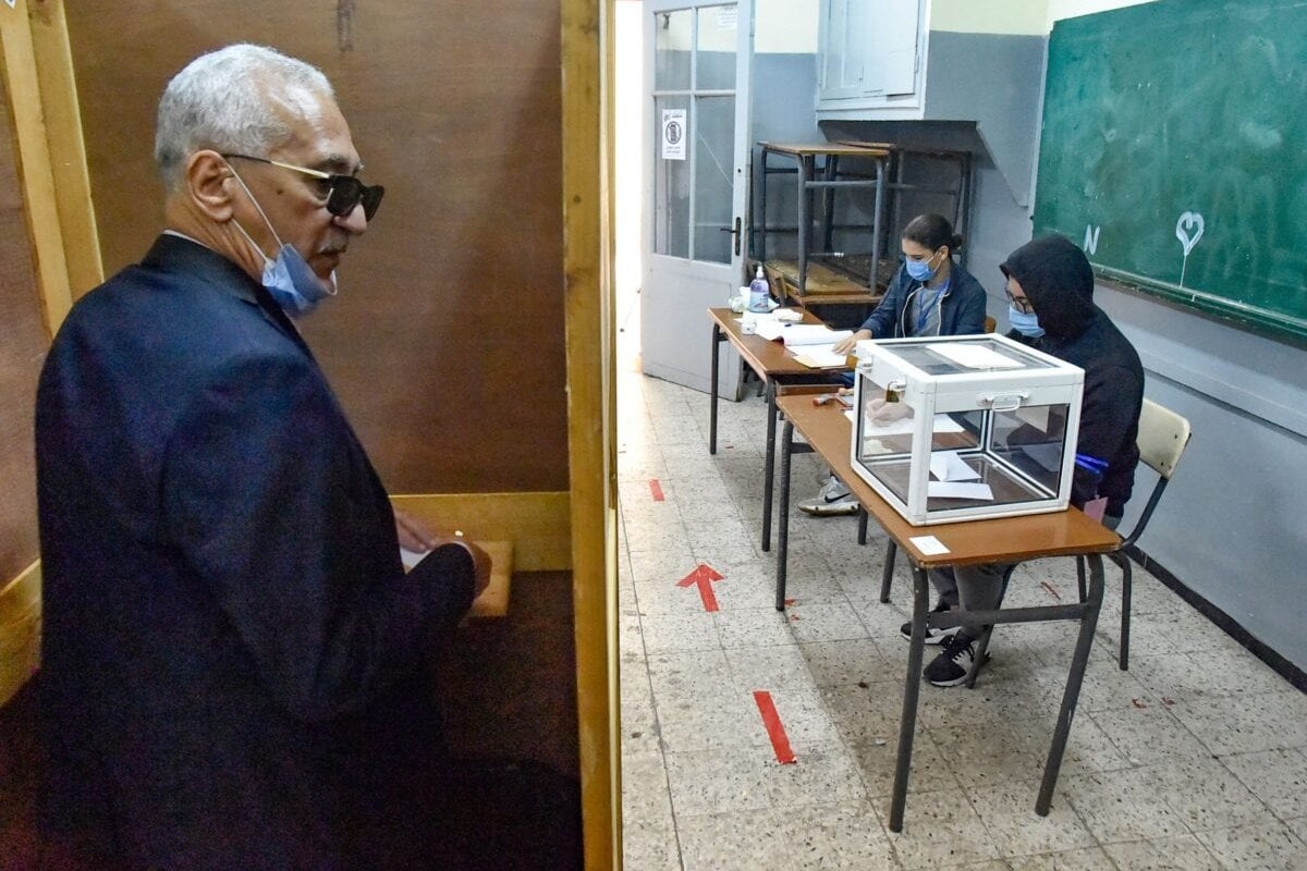 An Algerian man prepares to vote at a polling station in the capital Algiers on November 1, 2020 [RYAD KRAMDI/AFP via Getty Images]