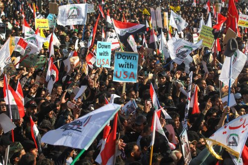Iraqi demonstrators lift flags and placards as they rally in Tahrir square in the capital Baghdad on 3 January 2021, to mark one year after a US drone strike killed Iran's revered commander Qasem Soleimani and his Iraqi lieutenant Abu Mahdi al-Muhandis near the capital. [AHMAD AL-RUBAYE/AFP via Getty Images]