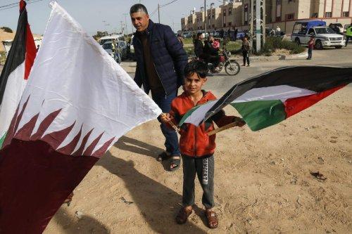 A Palestinian boy waves the Qatari and Palestinian flags on February 8, 2021 [SAID KHATIB/AFP via Getty Images]