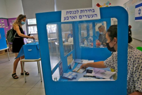 An Israeli voter casts her ballot at a polling station in the coastal city of Tel Aviv on March 23, 2021 [GIL COHEN-MAGEN/AFP via Getty Images]