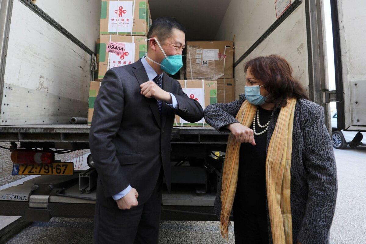 Chinese Ambassador Guo Wei (L) and Palestinian Health Minister Mai al-Kaila bump elbows during the unloading of a shipment of the Sinopharm COVID-19 vaccines donated by the Chinese government in the city of Ramallah in the West Bank, on March 29, 2021 [ABBAS MOMANI/AFP via Getty Images]