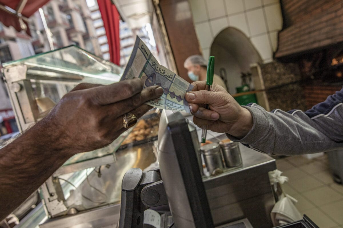 A customer hands over a Lebanese pound banknote in a bakery on Hamra Street in Beirut, Lebanon, on Tuesday, April 13, 2021 [Francesca Volpi/Bloomberg via Getty Images]
