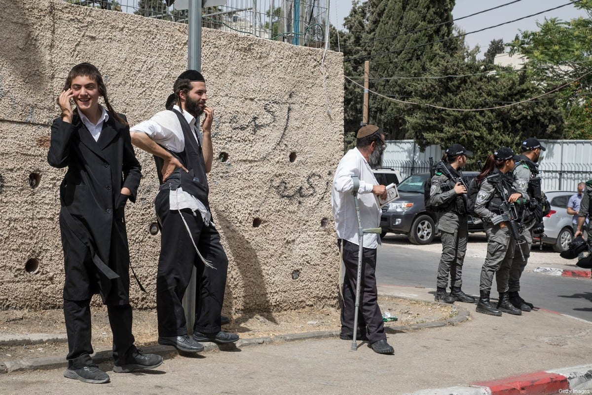 Jewish men stand on a corner with Israeli police in the neighborhood of Sheikh Jarrah during Israel's 'Jerusalem Day' on May 10, 2021 in Jerusalem, Israel. The Israeli national holiday, which celebrates the unification of Jerusalem under Israel's control following the 1967 Six-Day War, comes amid protests over the potential eviction of Palestinian families from Jerusalem's Sheikh Jarrah neighborhood. The Israeli Supreme Court was expected to rule today on whether to uphold a lower court's decision in a longstanding legal dispute between the resident families and Jewish settlers who claim ownership of the land, but the court delayed its decision for up to 30 days due to a request from the attorney general. (Photo by Laurent Van Der Stockt/Getty Images)