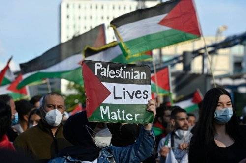 """A demonstrator displays a placard reading: """"Palestinian Lives Matter"""" during a pro-Palestinian protest in Berlin on May 19, 2021 [JOHN MACDOUGALL/AFP via Getty Images]"""