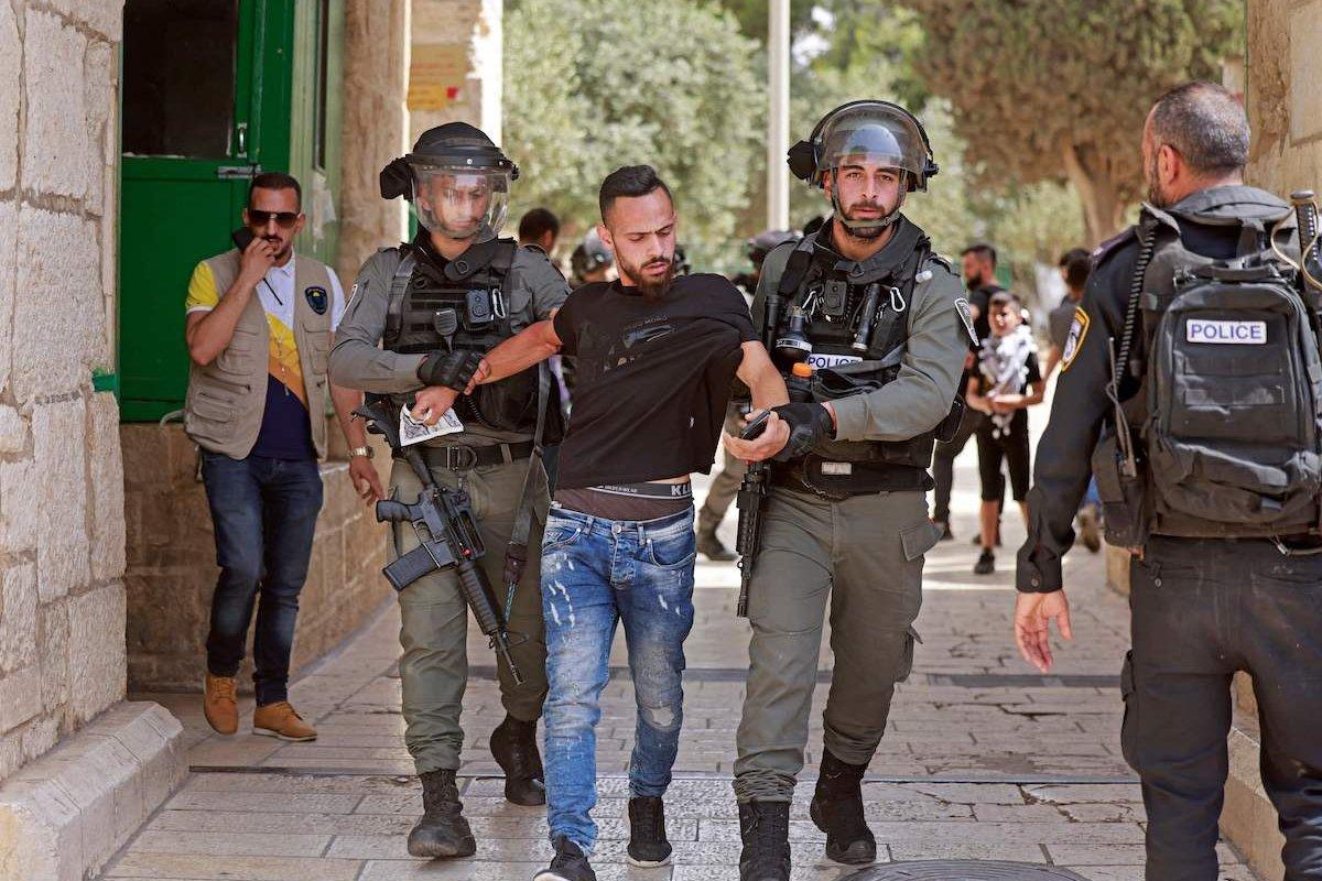 Israeli security forces detain a man at the entrance of Jerusalem's al-Aqsa mosque compound, on 21 May 2021 [MENAHEM KAHANA/AFP via Getty Images]