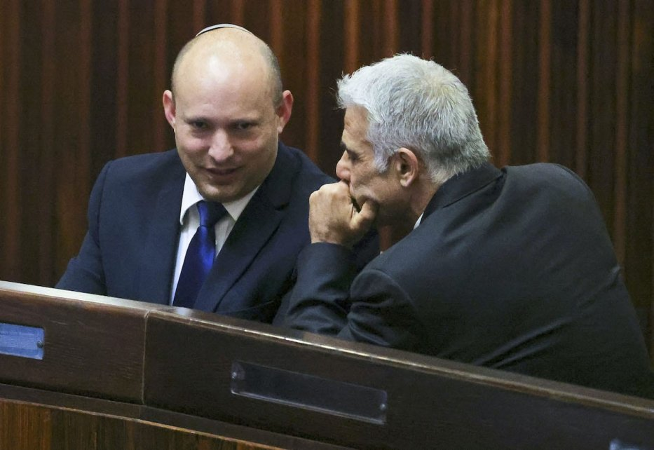 Israel's Yamina party leader, Naftali Bennett (L), smiles as he speaks to Yesh Atid party leader, Yair Lapid, during a special session of the Knesset, Israel's parliament, to elect a new president, in Jerusalem on 2 June 2021. [RONEN ZVULUN/POOL/AFP via Getty Images]