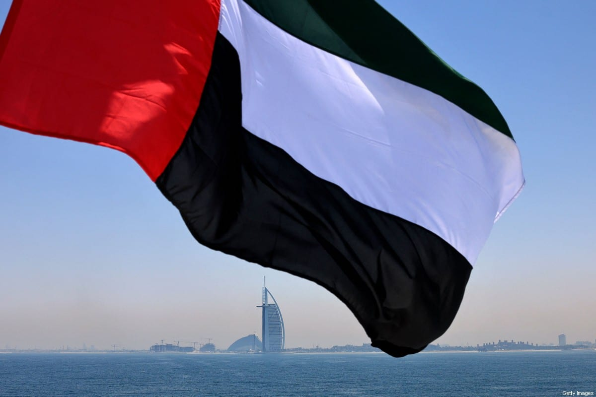 This picture taken on June 3, 2021 shows an Emirati flag fluttering above Dubai's marina with the Burj Al Arab landmark hotel (C) in the background [KARIM SAHIB/AFP via Getty Images]