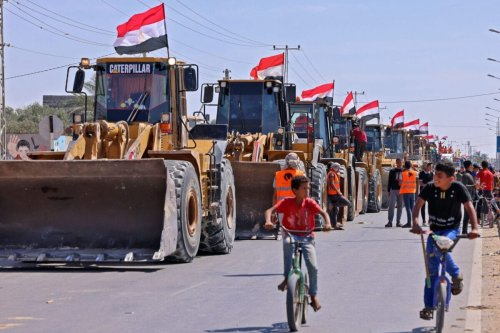 Palestinian boys cycle past a convoy of bulldozers provided by Egypt arriving at the Palestinian side of the Rafah border crossing between Egypt and the Palestinian Gaza Strip enclave on June 4, 2021 [SAID KHATIB/AFP via Getty Images]