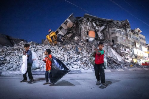 Palestinian boys walk past the destroyed Al-Shuruq tower in Gaza on June 7, 2021 [MOHAMMED ABED/AFP via Getty Images]