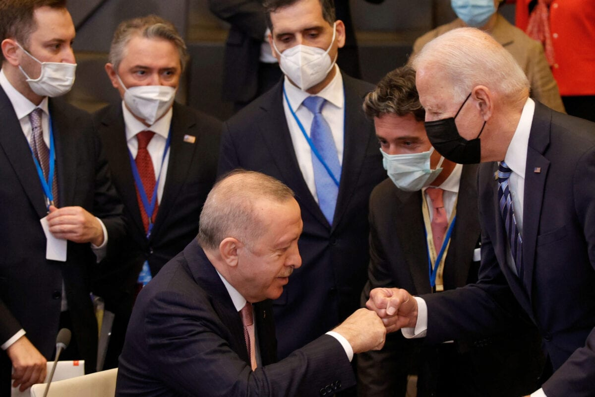 TOPSHOT - CAPTION CLARIFICATION - Turkey's President Recep Tayyip Erdogan (C) fist bumps with U.S. President Joe Biden (R) as he stands up to greet him during a plenary session at a NATO summit in Brussels, Monday, June 14, 2021. U.S. - The allies will agree a statement stressing common ground on securing their withdrawal from Afghanistan, joint responses to cyber attacks and relations with a rising China. - CAPTION CLARIFICATION (Photo by Olivier Matthys / POOL / AFP) / CAPTION CLARIFICATION (Photo by OLIVIER MATTHYS/POOL/AFP via Getty Images)