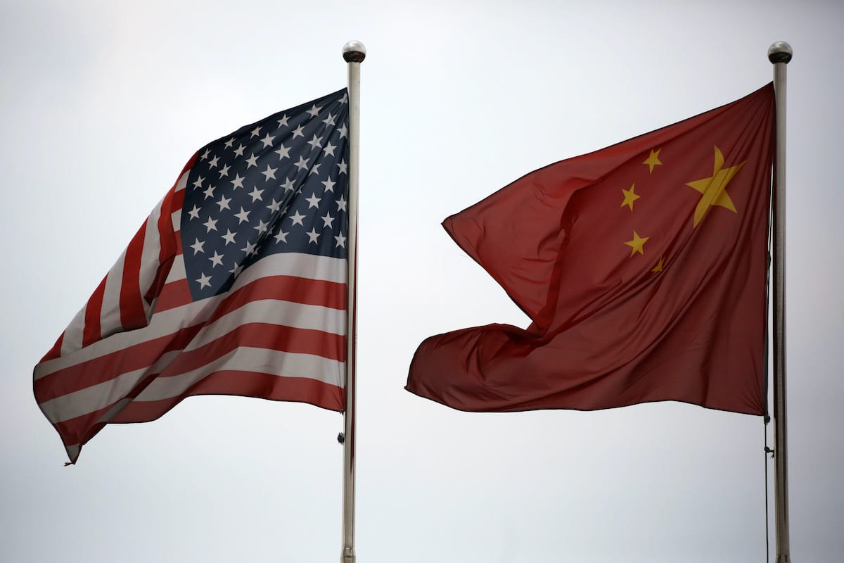 US and Chinese national flags fly outside a company building in the China (Shanghai) Pilot Free Trade Zone's Waigaoqiao free trade zone and logistics park in Shanghai, China, on Tuesday, 22 Oct. 2013. [Tomohiro Ohsumi/Bloomberg via Getty Images]