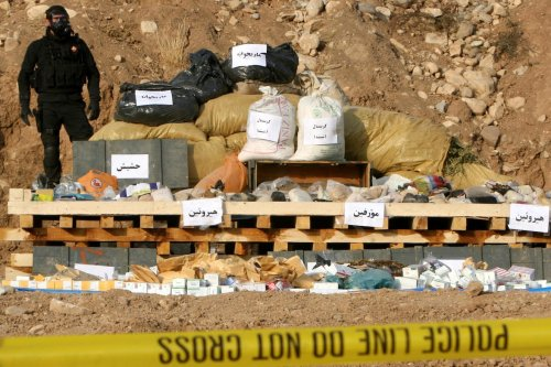 A member of the Iraqi Kurdish security forces stands next to seized drug before its destruction on October 29, 2013 in the Iraqi northern city of Arbil. [SAFIN HAMED/AFP via Getty Images]
