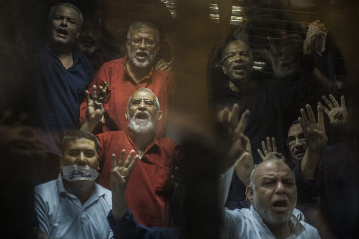 Egyptian Muslim Brotherhood leader Mohamed Badie (C) gestures from behind the defendant's cage as the judge reads out the verdict sentencing him and more than 100 other defendants in Cairo on May 16, 2015 [KHALED DESOUKI/AFP via Getty Images]