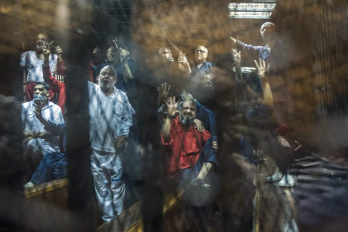 Egyptian Muslim Brotherhood top figure Mohamed el-Beltagi (C) gestures from behind the defendant's cage as the judge reads out the verdict sentencing him and more than 100 other defendants, to death at the police academy in Cairo on May 16, 2015. [KHALED DESOUKI/AFP via Getty Images]