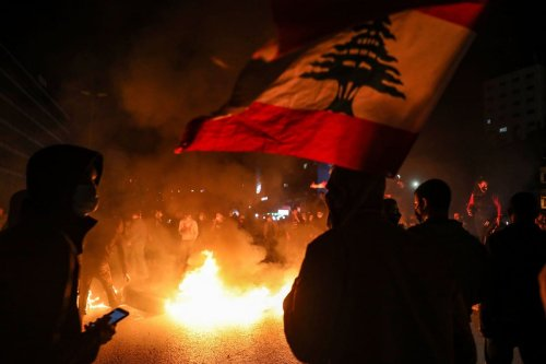 Demonstrators wave the Lebanese national flag at a protest against the the deteriorating economic and social conditions in Beirut, Lebanon on 2 March 2021 [ANWAR AMRO/AFP/Getty Images]