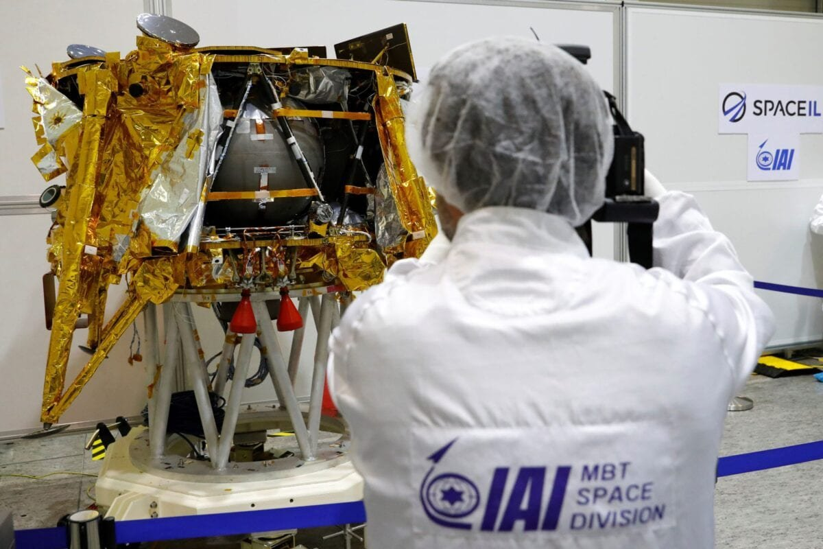 A foreign journalist films a spacecraft weighing some 585 kilogrammes (1,300 pounds) during a presentation by Israeli nonprofit SpaceIL and Israeli state-owned Aerospace Industries, on December 17, 2018 in Yehud, east of Tel Aviv [JACK GUEZ/AFP via Getty Images]