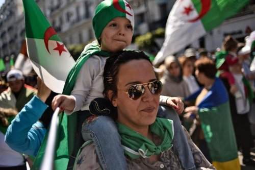 An Algerian woman carries a child on her back in Algiers on March 29, 2019 [RYAD KRAMDI/AFP via Getty Images]
