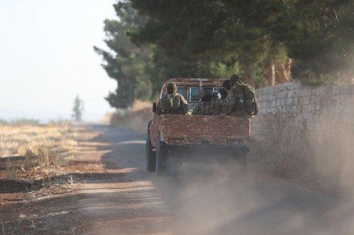 Fighters from the former al-Qaeda Syrian affiliate Hayat Tahrir al-Sham (HTS) drive through the village of Hamameyat on the border between Hama and Idlib provinces on July 11, 2019. [OMAR HAJ KADOUR/AFP via Getty Images]
