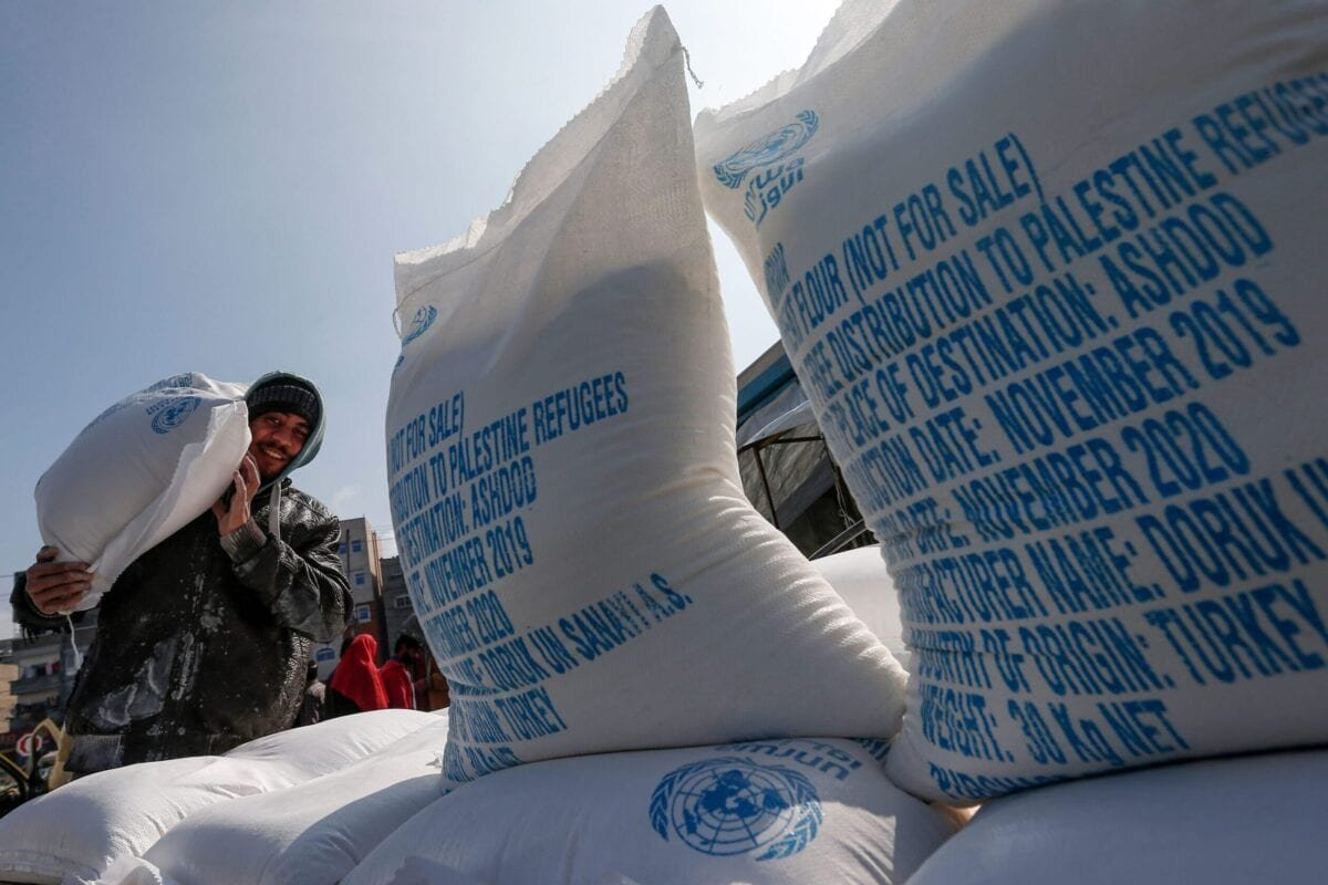 A Palestinian man carries on his shoulder sacks of flour received from a United Nations Relief and Works Agency (UNRWA) distribution centre in Jabalia refugee camp in the northern of Gaza Strip , on 29 January 2020 [MAHMUD HAMS/AFP via Getty Images]