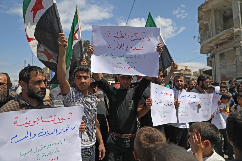 Syrian demonstrators rally in the town of Binnish in Syria's northwestern Idlib province on 1 May 2020, to protest against a reported attack by Hayat Tahrir al-Sham, an alliance led by a former Al-Qaeda affiliate, on a protest the previous day. [OMAR HAJ KADOUR/AFP via Getty Images]
