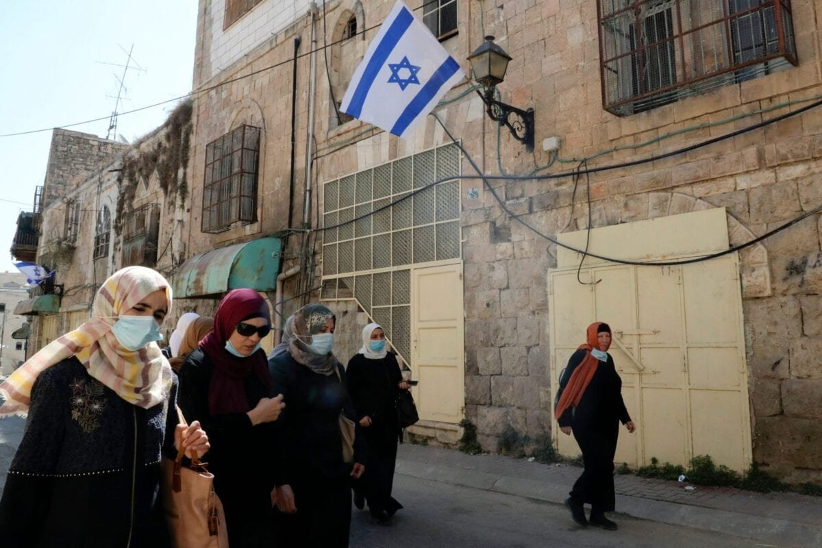 Palestinian women walk toward their houses in al-Shuhada street, which is largely closed to Palestinians, in the city centre of the West Bank town of Hebron, on September 24, 2020 [HAZEM BADER/AFP via Getty Images]