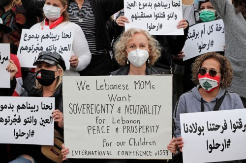 Lebanese women hold placards as they protest against the country's political paralysis and deep economic crisis in Beirut on the occasion of Mother's Day, on 20 March 2021. [ANWAR AMRO/AFP via Getty Images]
