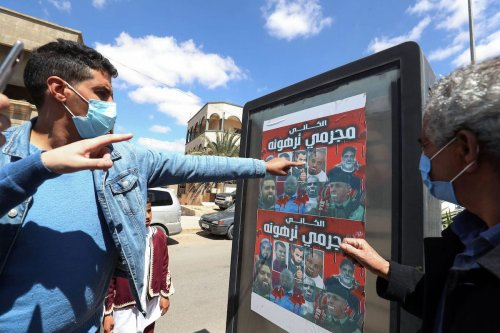 """Libyans look at a poster depicting members of a family who commanded a militia that traumatised Tarhuna town with the Arabic phrase """"al-Kani, Tarhuna's criminals"""", during a funeral procession for 12 bodies that were identified from mass graves found in Tarhuna town, 80Km southeast of the capital, on 26 March 2021. [MAHMUD TURKIA/AFP via Getty Images]"""