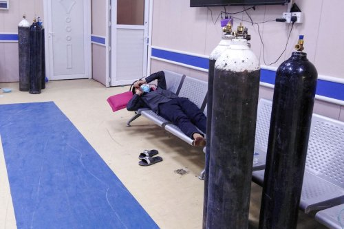 An Iraqi COVID-19 patient lies down in a waiting hall next to oxygen bottles at the Ibn Al-Khatib Hospital in Baghdad, on 25 April 2021 [AHMAD AL-RUBAYE/AFP via Getty Images]