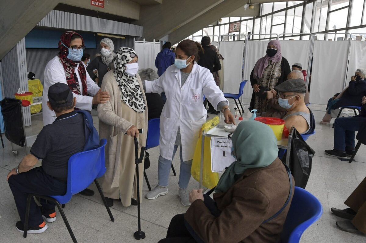 Tunisian healthcare workers assist an elderly woman during inoculation at El-Menzah sports hall in Tunisia's capital Tunis on May 3, 2021 [FETHI BELAID/AFP via Getty Images]