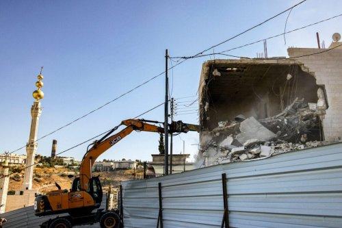 An excavator demolishes homes on June 22, 2021 [AHMAD GHARABLI/AFP via Getty Images]