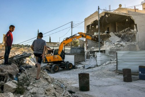 An excavator commissioned by Palestinian Jerusalem resident Ahmed Obaid demolishes Obaid's home in the mostly-Arab east Jerusalem neighbourhood of Issawiya on June 22, 2021 [AHMAD GHARABLI/AFP via Getty Images]