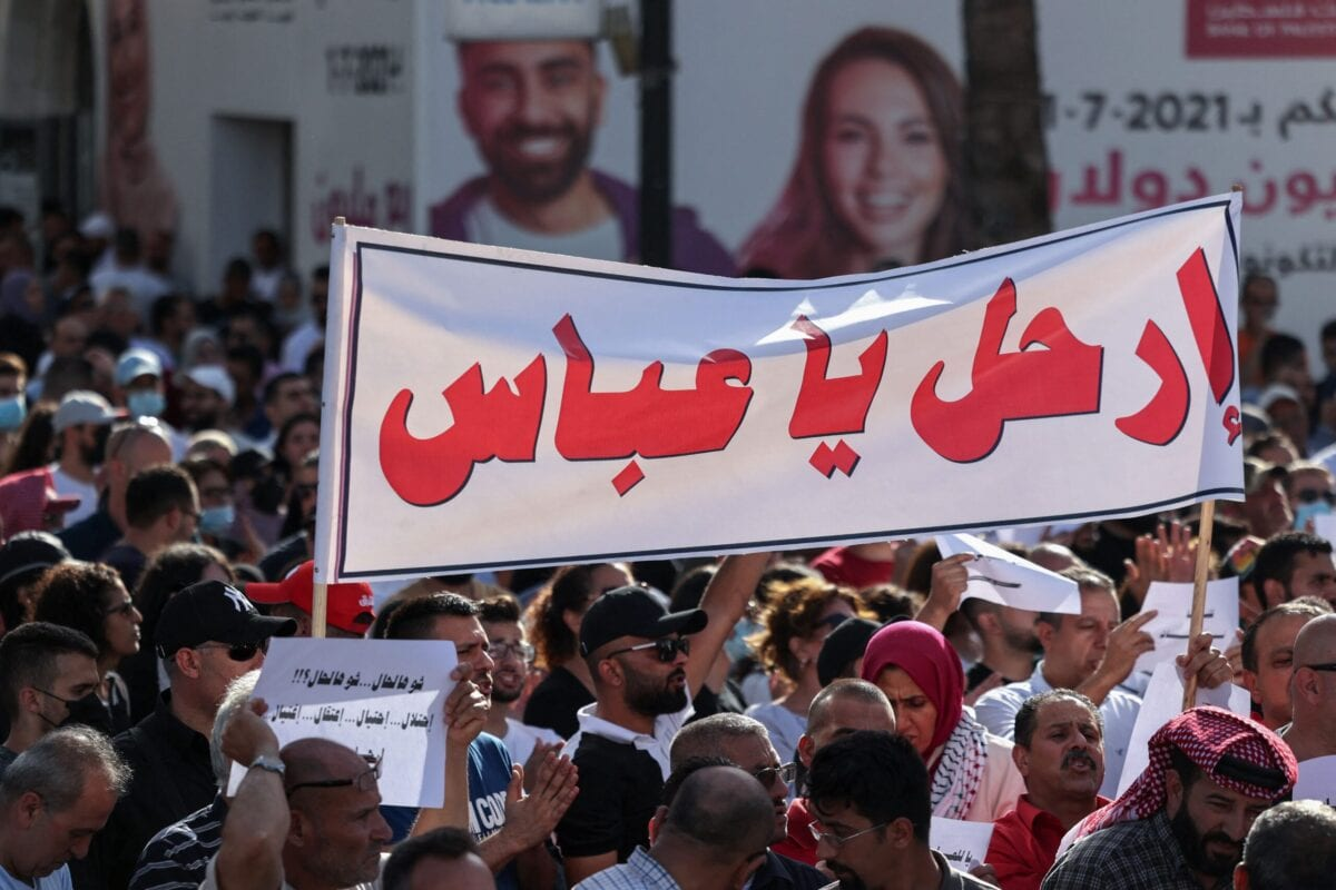 """Palestinians lift placards in Arabic which read """"What a situation: Occupation... deceit... arrest... assassination"""" as a banner addressing Palestinian President Mahmoud Abbas reads """"Leave"""" in Ramallah city in the occupied West Bank on July 3, 2021 [ABBAS MOMANI/AFP via Getty Images]"""