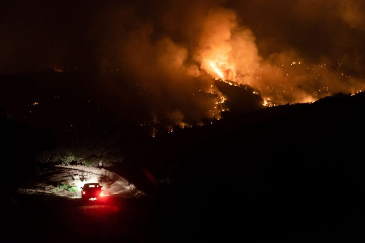 A car drives on a road in the village of Vavatsinia in the Larnaca district of Cyprus, as a giant wildfire rages on the hills above, during the night of July 3, 2021 [IAKOVOS HATZISTAVROU/AFP via Getty Images]