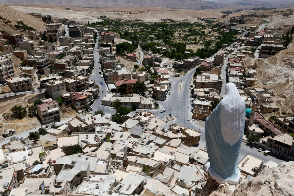 A statue of the Virgin Mary overlooks the village of Maalula, north of the Syrian capital Damascus, on June 29, 2021 [LOUAI BESHARA/AFP via Getty Images]