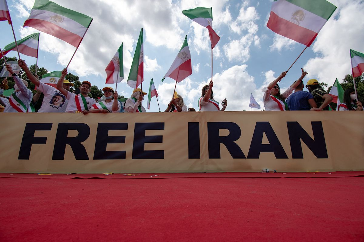 Demonstrators take part in a protest called by the National Council of Resistance of Iran (NCRI) against the Iranian regime in front of the Brandenburg Gate in Berlin on 10 July 2021. [PAUL ZINKEN/AFP via Getty Images]