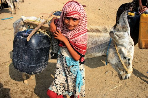 A girl stands by a donkey carrying jerrycans of water filled from a cistern at a make-shift camp for the internally displaced in Yemen's northern Hajjah province on 12 July 2021, amidst an extreme heat wave and severe water shortage. [ESSA AHMED/AFP via Getty Images]