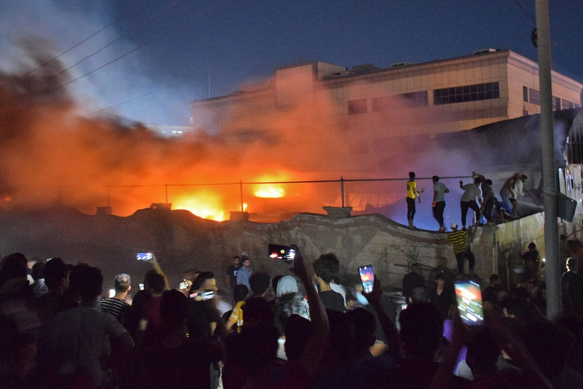 People gather as a massive fire engulfs the coronavirus isolation ward of Al-Hussein hospital in the southern Iraqi city of Nasiriyah, late on July 12, 2021 [ASAAD NIAZI/AFP via Getty Images]