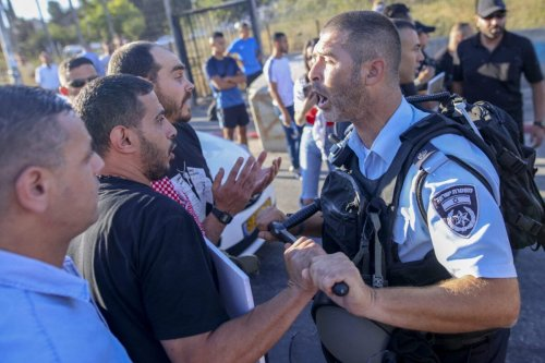 A Palestinian protester scuffles with a member of Israeli security forces near an Israeli roadblock at the entrance of the Sheikh Jarrah neighbourhood in east Jerusalem during a rally against the planned expulsion of Palestinians from houses there, on July 17, 2021 [AHMAD GHARABLI/AFP via Getty Images]