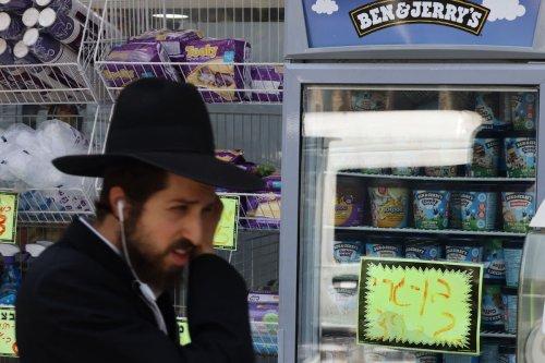 An Ultra Orthodox Jewish man walks by Ben & Jerry's ice cream in Jerusalem on July 20, 2021. [AHMAD GHARABLI/AFP via Getty Images]